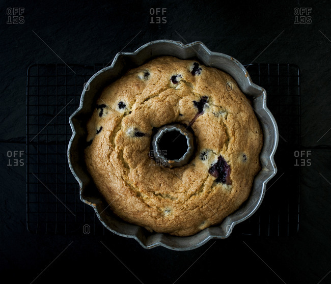 Blueberry pound cake on cooling rack with dark slate background