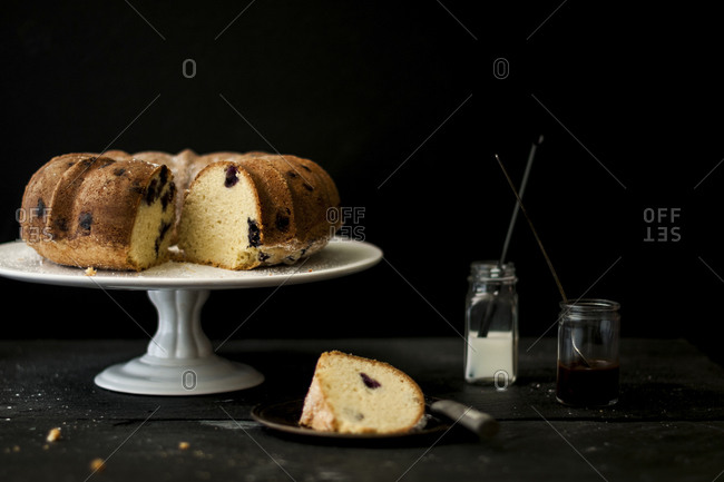 Blueberry pound cake with a slice removed and sauces
