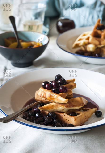 Two plates of waffles with blueberries and maple syrup