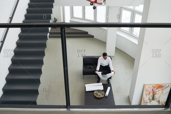 High angle view of man looking at blueprints