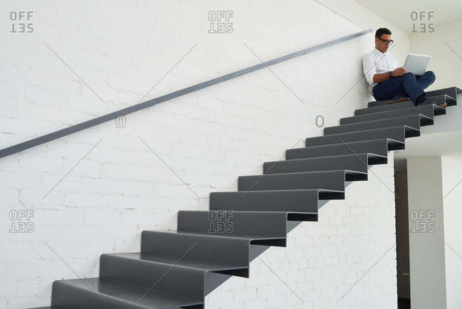 Man using a laptop while sitting on stairs
