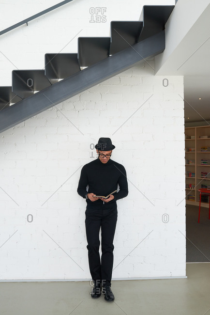 Man under stairs reading a book