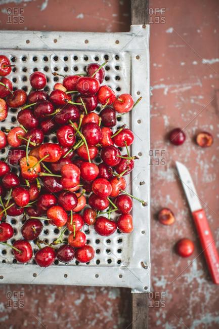Overhead view of fresh cherries on enameled metal grid