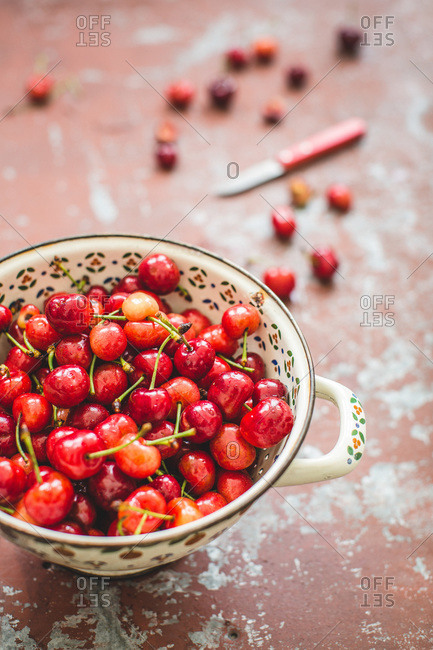 Elevated view of fresh cherries in a handled bowl