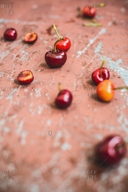 Fresh cherries scattered on a weathered painted surface