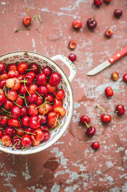 Overhead view of fresh cherries in a handled bowl on rustic surface