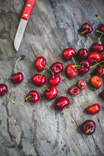 Overhead view of fresh cherries on wooden surface with knife
