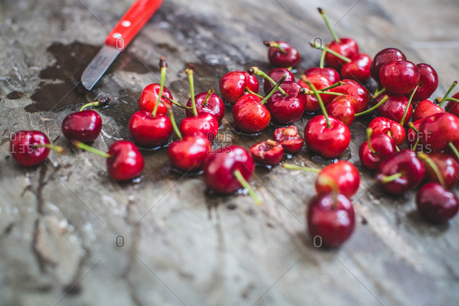 Freshly washed cherries on wooden surface with knife