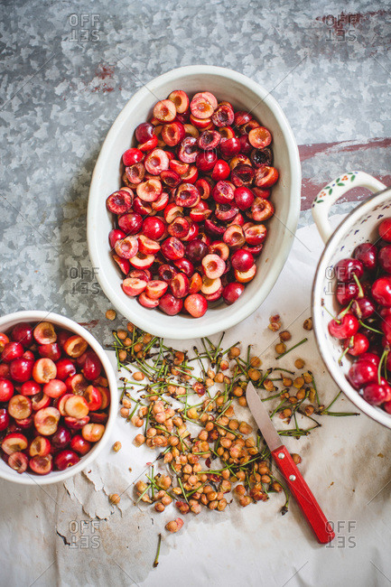 Overhead view of containers of pitted cherries with knife
