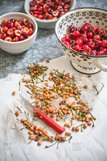 Pits and stems with knife and bowls of cherries