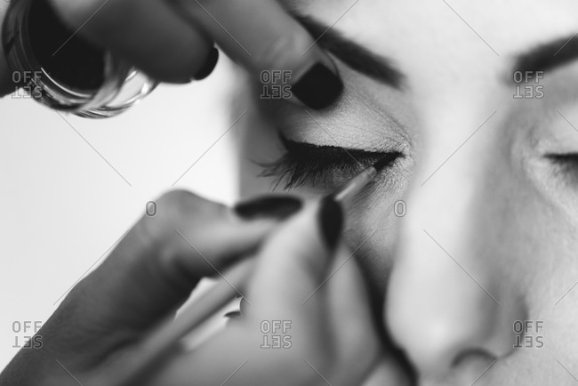 Hands applying makeup to a woman's eyes