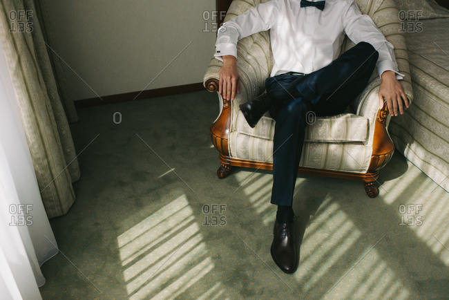 Groom in a tux sitting in an armchair on his wedding day