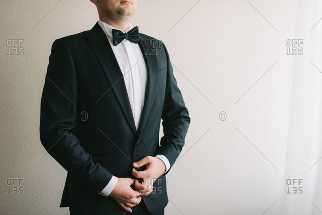 Groom buttoning his tuxedo on his wedding day