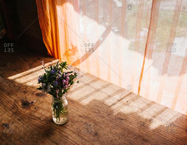A bouquet of flowers in a glass jar sitting near a window