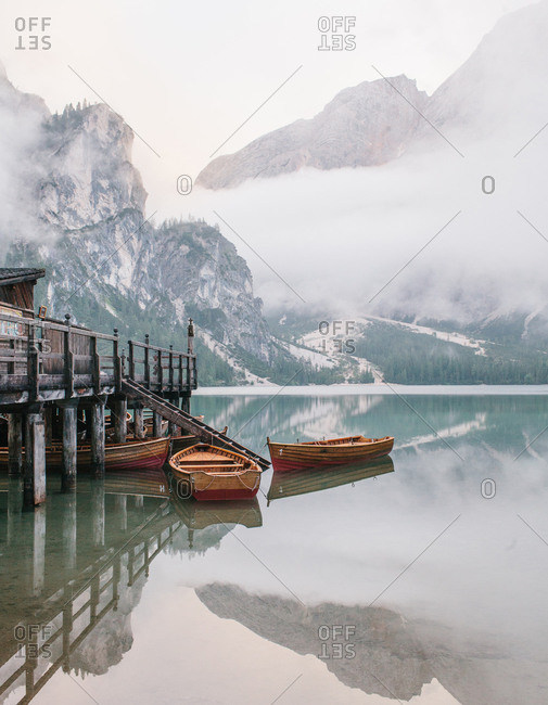 Wood row boats anchored beside a dock on a glassy lake in the Dolomites in Italy