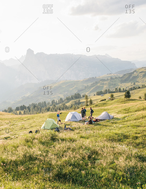 People setting up tents on a sunlit hillside in the Dolomites in Italy