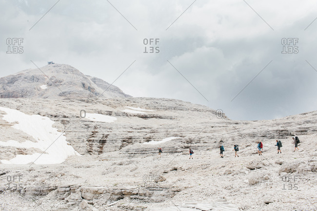 Hikers traverse a section of the snow covered Dolomites in Italy