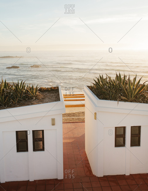 Two small white buildings on the edge of a sandy beach