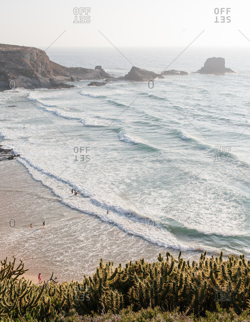 Aerial view of people wading into the surf at a beach