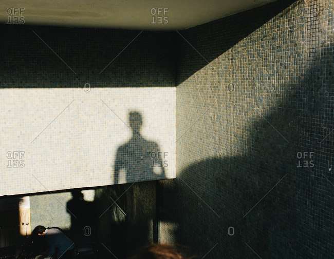 A person's shadow on a tile wall