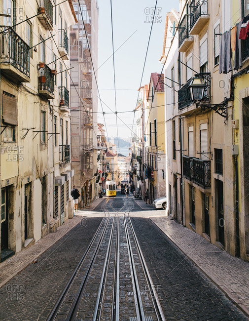 Trolley tracks and wires running down the middle of a narrow city street
