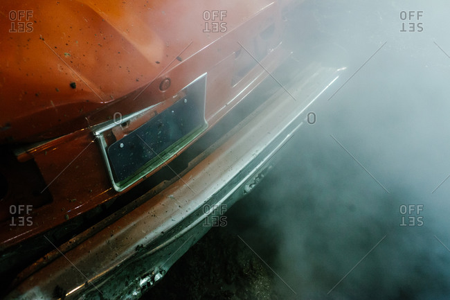 Close-up of a car bumper shrouded in smoke at Warneton Raceway in Belgium