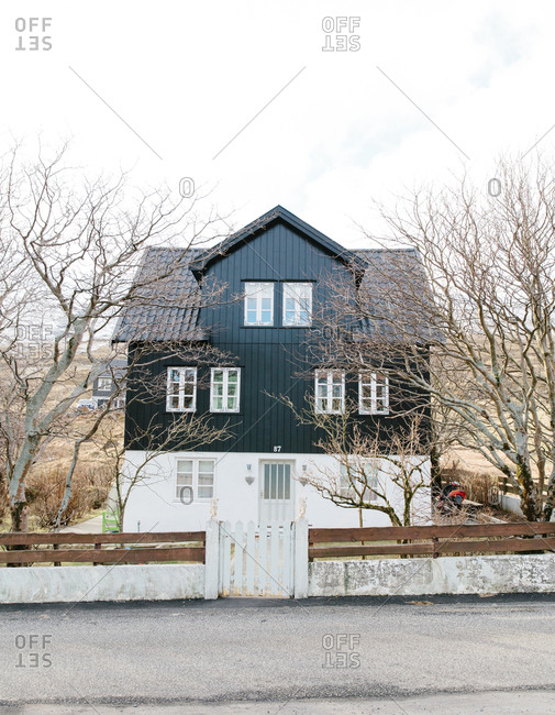 Small house surrounded by trees along a rural road in the Faroe Islands