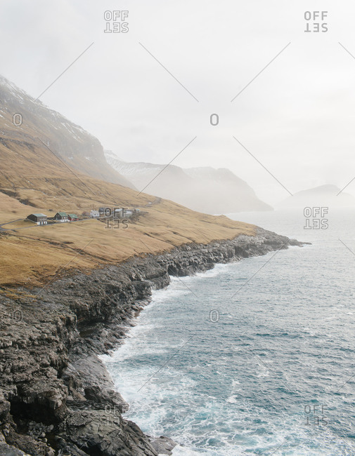 A village nestled along a rugged coastal hillside in the Faroe Islands