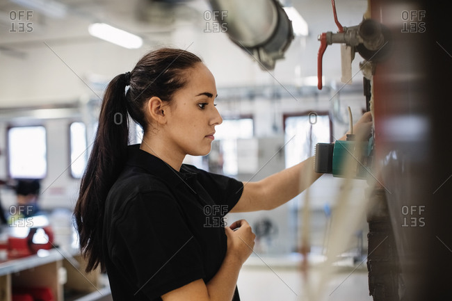 Side view of female auto mechanic student analyzing machinery at workshop