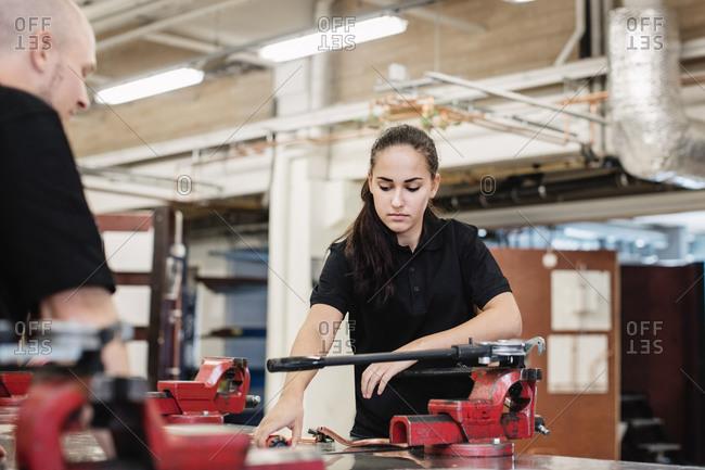 Auto mechanic teacher assisting female student in workshop