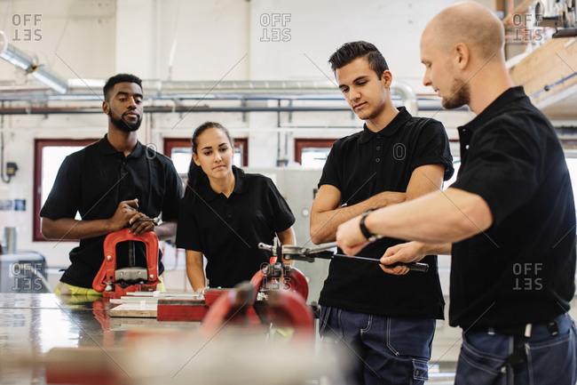 Auto mechanic teacher explaining equipment to students in class