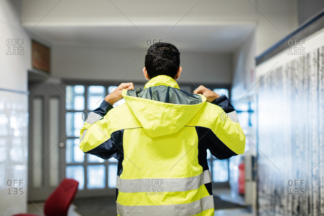 Rear view of auto mechanic student wearing reflective jacket in workshop