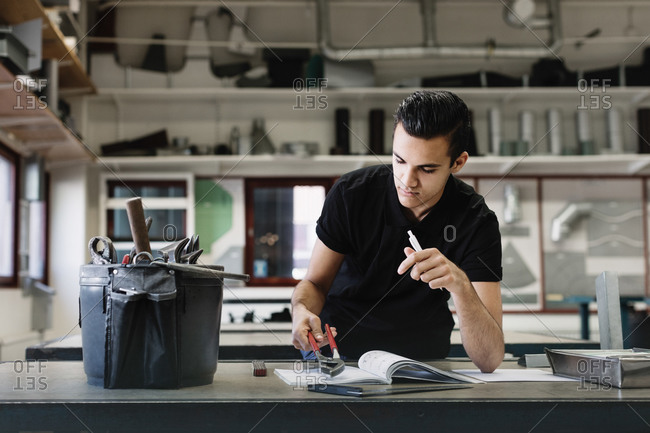 Male high school student examining pliers at table in workshop
