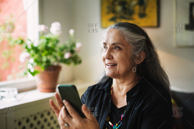 Happy senior woman using mobile phone at home
