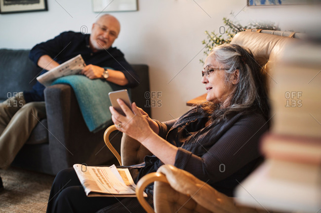 Senior woman showing mobile phone to man at home