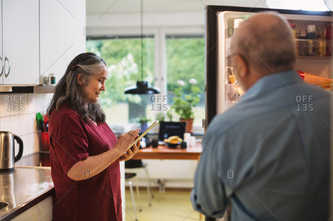 Side view of senior woman using digital tablet while man standing at refrigerator