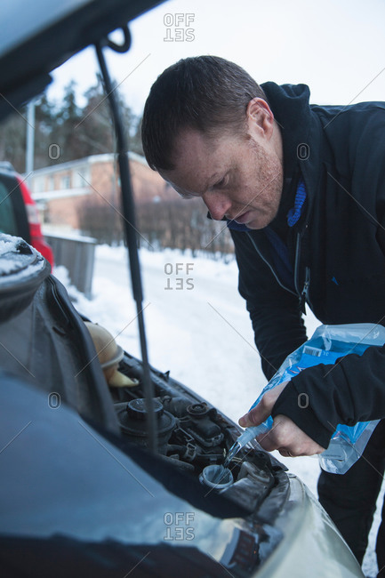 Mature man pouring windshield washer fluid into car during winter