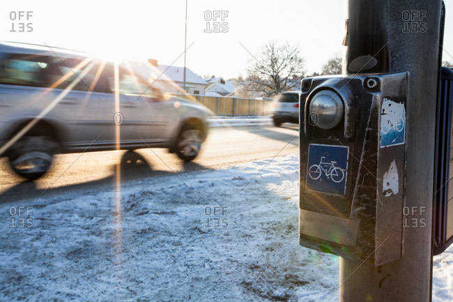Blurred motion of car passing by bicycle crossing sign during winter