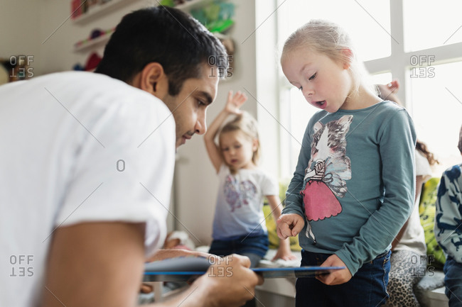 Male teacher and girl looking at book in day care center