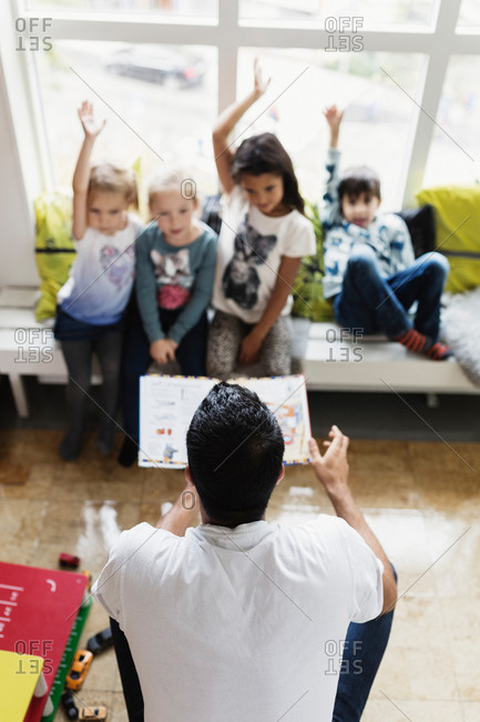 High angle view of male teacher asking questions to students at day care center