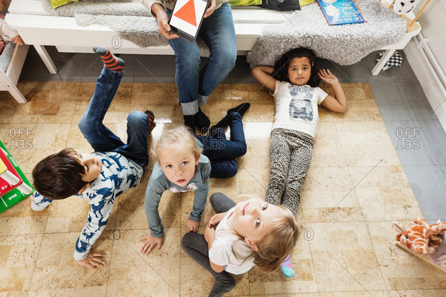 High angle view of children resting while teacher showing triangle on digital tablet