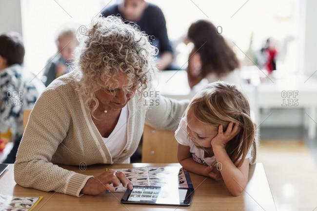 Senior teacher using digital tablet with student in preschool