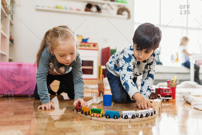 Little boy and girl playing with toy train at preschool