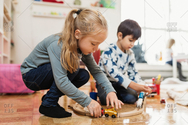 Boy and girl playing with toy train at preschool