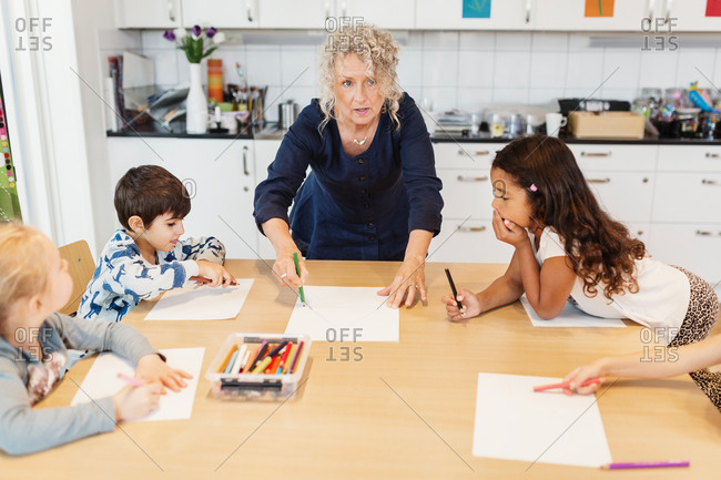 Senior female teacher with students in drawing class