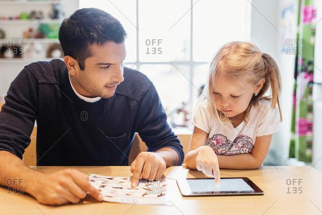 Mid adult male teacher looking at girl using digital tablet at preschool