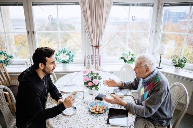 Senior man talking to caretaker at dining table in nursing home