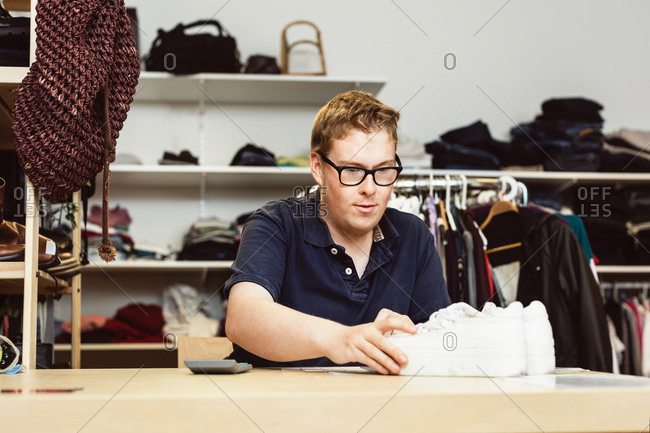 Cashier holding shoes on table while calculating in clothing store