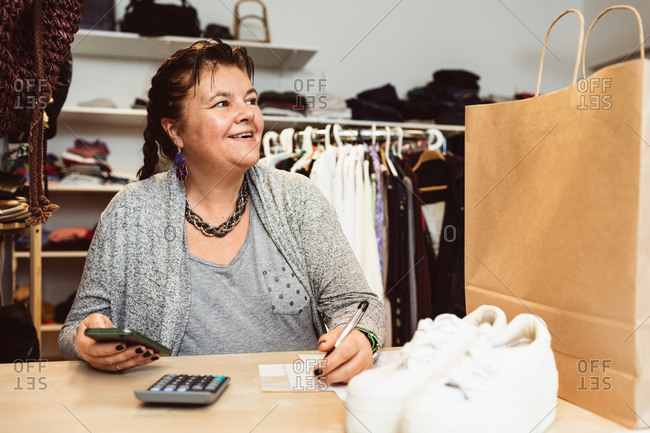 Smiling cashier counting with smart phone on checkout table in clothing store