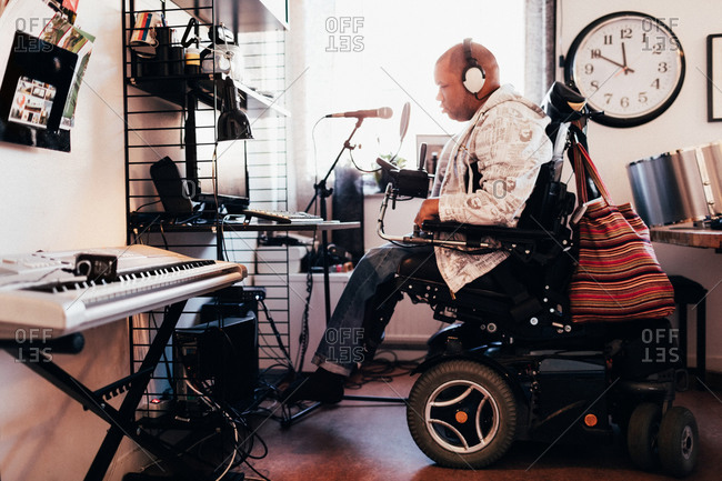 Side view of disabled musician with headphones in recording studio